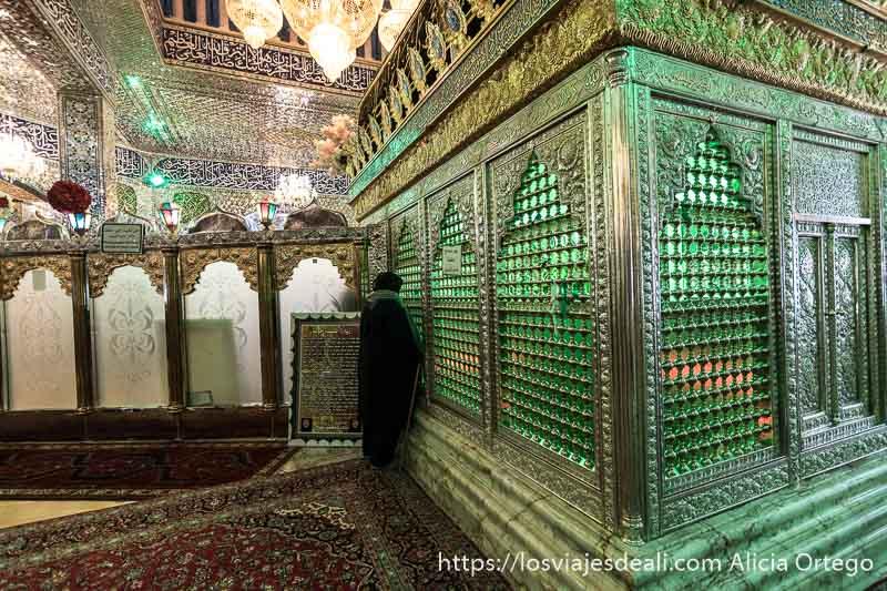 mausoleo de mezquita chií con mujer orando ante tumba que es como una jaula de plata en el valle de bekaa