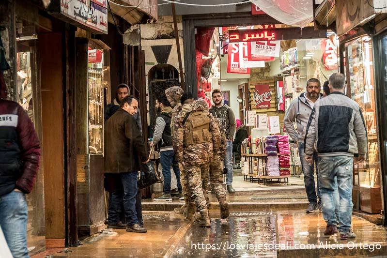soldados del ejército andando por una calle del zoco de trípoli cruzándose con otros hombres en día lluvioso