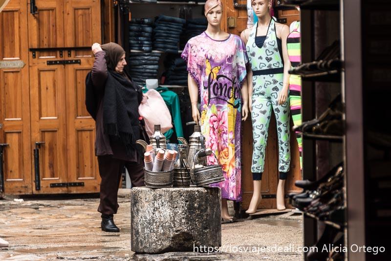 mujer con velo pasando delante de maniquíes con ropa colorida y cafeteras con vasitos sobre un soporte de piedra en el zoco de trípoli