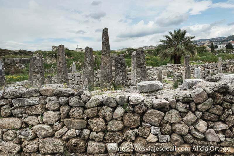 templo de los obeliscos asomando tras el muro de piedra en la ciudad antigua de byblos
