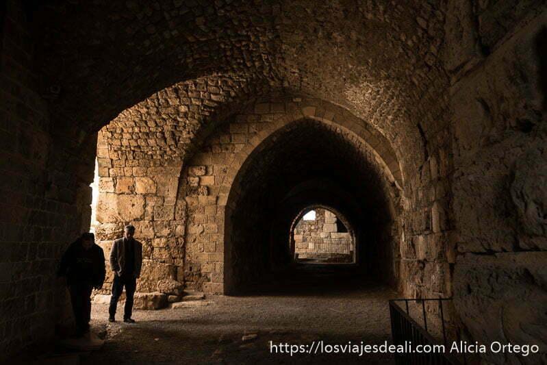 galería con bóvedas todo de piedra y un hombre entrando desde el patio en el castillo de los cruzados de byblos, sitios que ver en Líbano