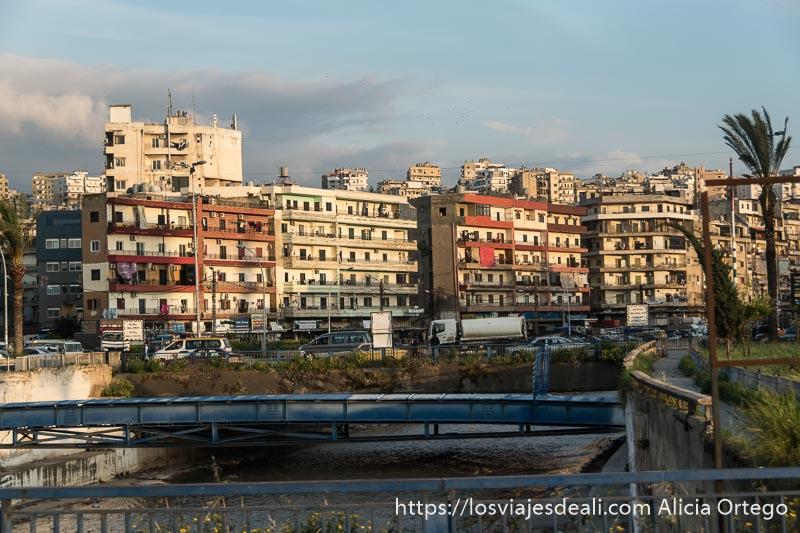 río de trípoli con puentes y mucho tráfico y al fondo edificios de varios pisos y una palmera