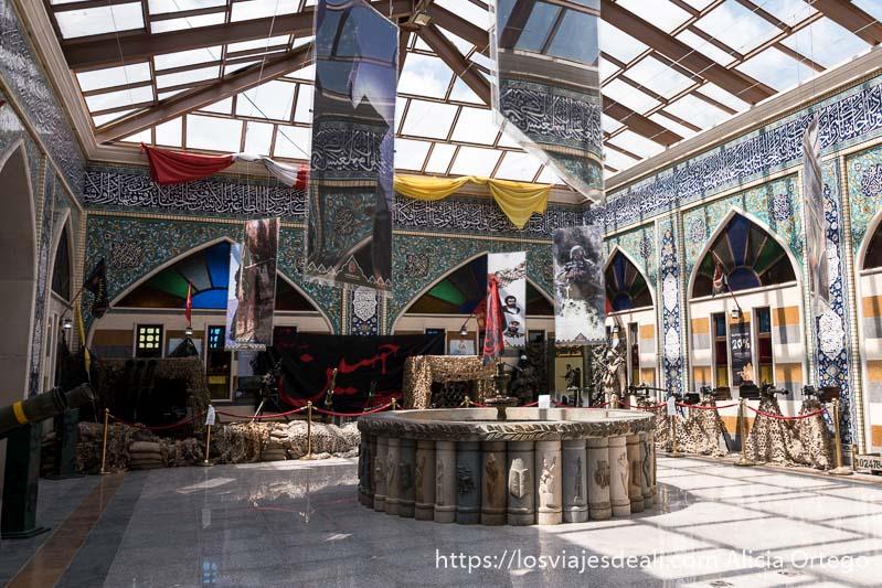 pati interior con metralletas y otras armas expuestas y una bandera negra con letras rojas en árabe en el valle de bekaa