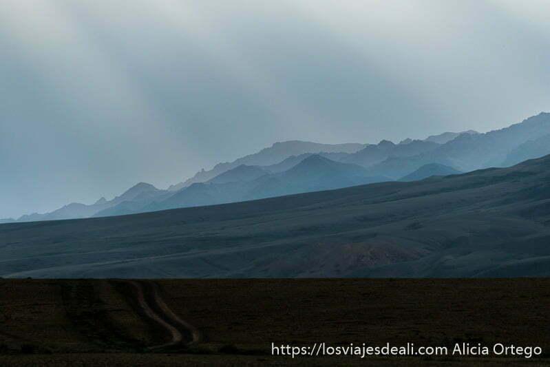 rayos de luz atraviesan las nubes e iluminan el paisaje de montañas y praderas verdes en mongolia