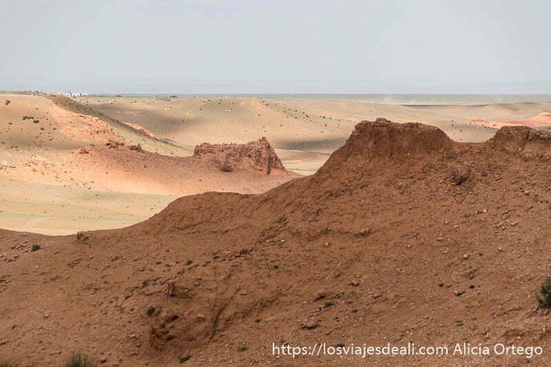 formaciones de arenisca con estepa verde al fondo en los flaming cliffs del viaje a mongolia