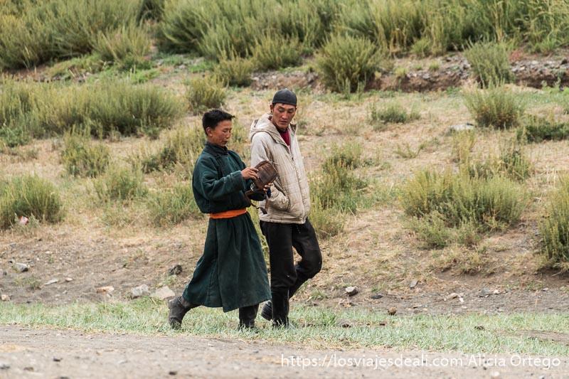 joven con raje tradicional de color verde y fajín naranja hablando con otro vestido a la occidental viajar a mongolia