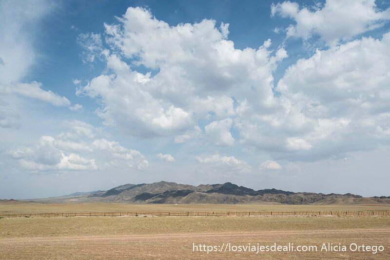 paisaje de prados con una valla de madera y montañas al fondo y mucho cielo con nubes blancas viajar a mongolia