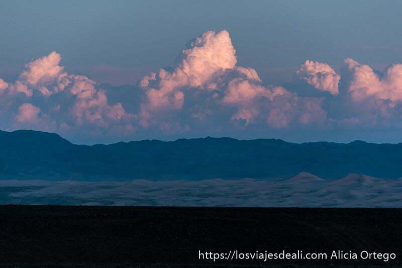 atardecer con grandes nubes coloreadas por el sol poniente y las montañas y dunas del desierto del gobi en el horizonte
