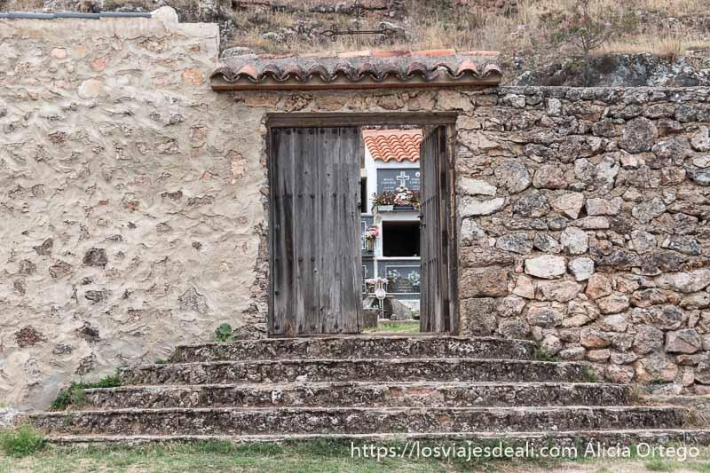 puerta de madera del cementerio con una hoja abierta por donde se ven los nichos escapada a albacete