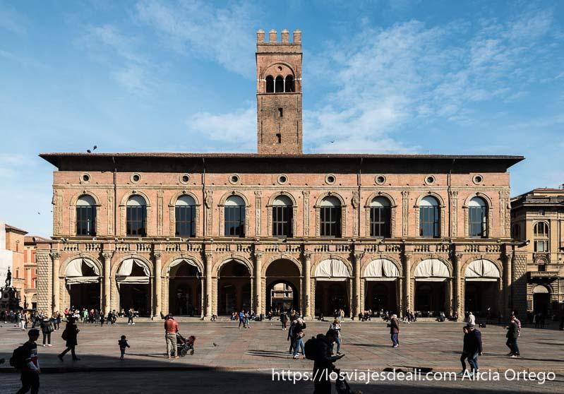 edificio del ayuntamiento con torre en el centro terminada en almenas con cielo azul imprescindibles de bolonia