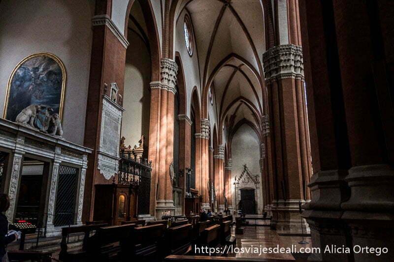 pasillo lateral de san petronio con enormes columnas de ladrillo y rayos de sol iluminándolas imprescindibles de bolonia