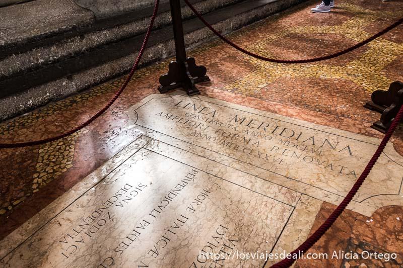 """placa de mármol en el suelo con leyenda """"línea meridiana"""" en san petronio de bolonia"""