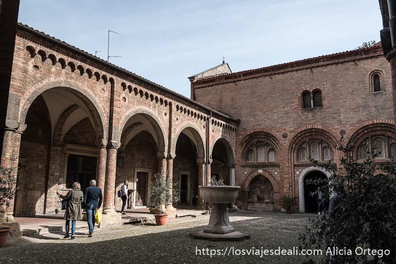 claustro de san estefano con pila bautismal muy grande en el centro imprescindibles de bolonia