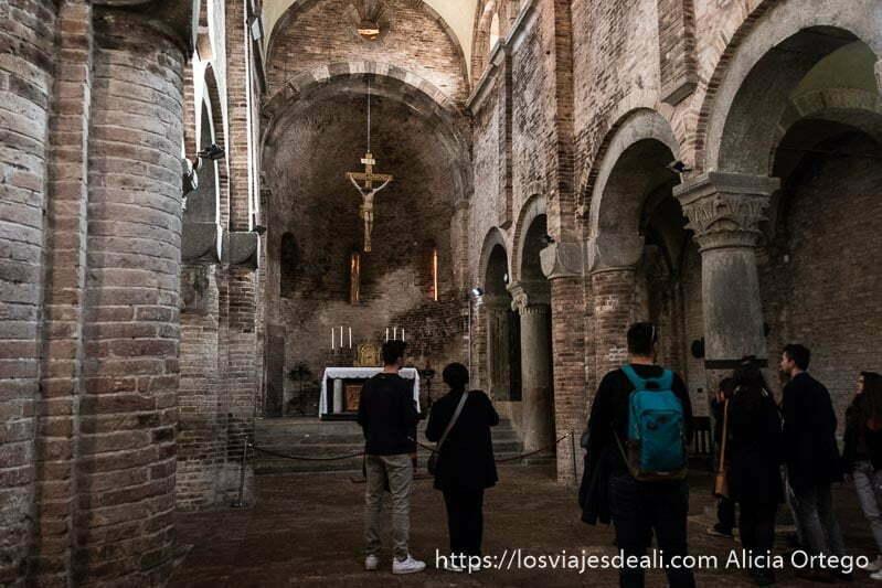 nave de una de las iglesias de san stefano con altar con cristo en la cruz colgando del techo imprescindibles de bolonia