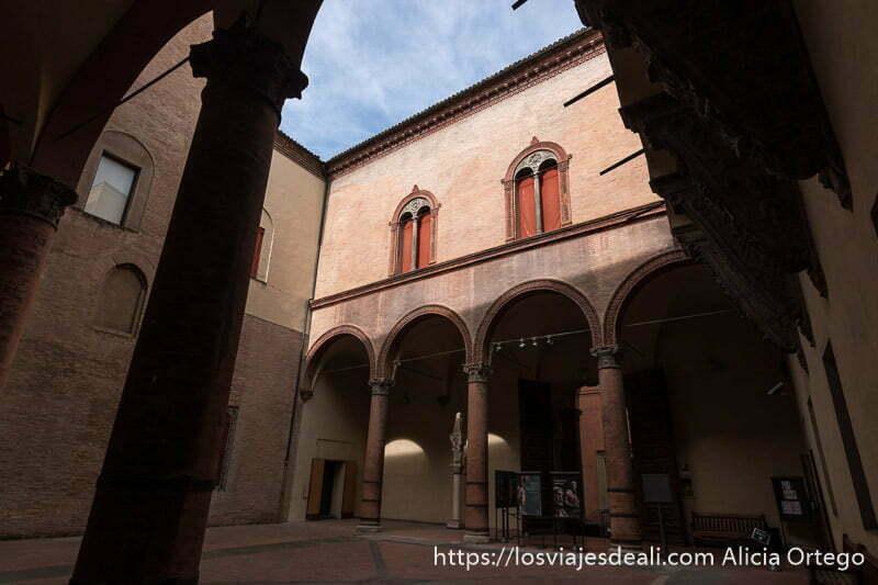 patio del palacio donde está el museo medieval de bolonia con ventanas con arcos divididas por columna