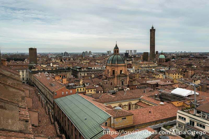 vistas de la terraza de san petronio con cúpula de iglesia y al fondo torre asinelli destacando en el cielo nublado imprescindibles de bolonia