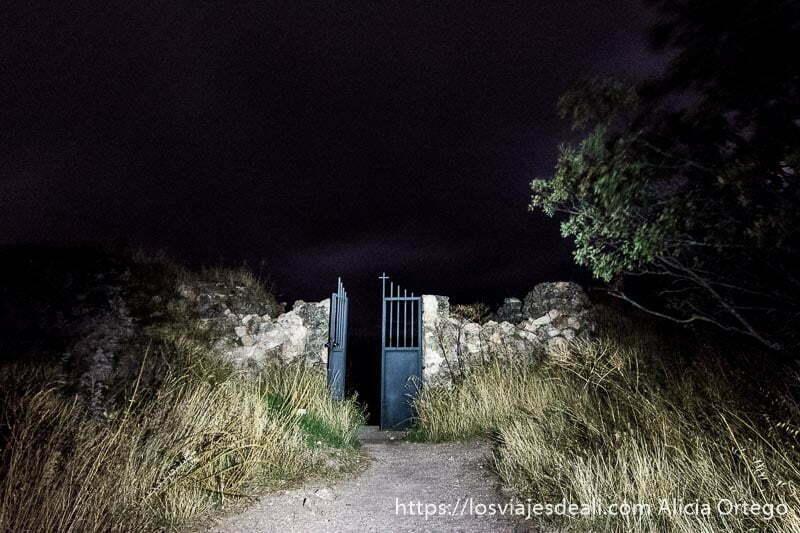 puerta del cementerio de riópar viejo de metal con cruz y valla de madera en la noche