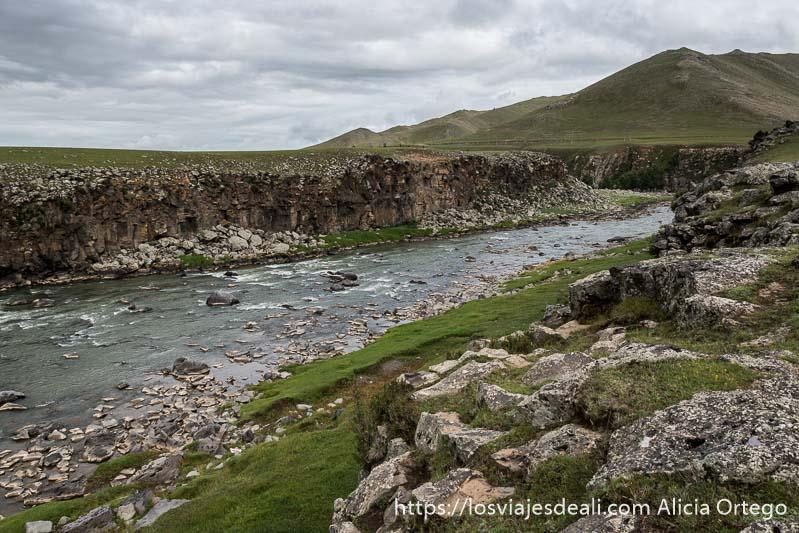 río orkhon entre paredes de roca con colinas verdes al fondo y muchas nubes de tormenta en el valle de orkhon