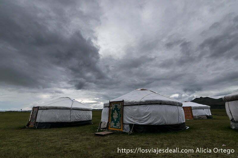 campamento de gers blancos con puertas de madera pintadas de colores y nubes de tormenta en el valle de orkhon