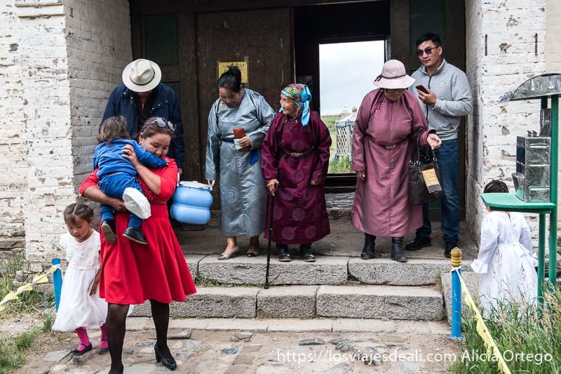 familia mongol con dos abuelas y dos niños con vestidos de seda entrando en el patio del templo tibetano de karakorum