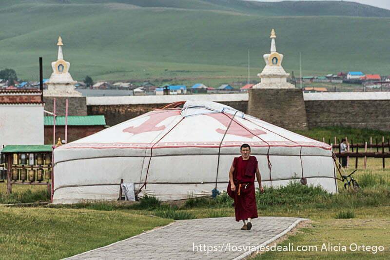 monje budista avanzando por un camino con gran ger blanco detrás y las murallas de karakorum al fondo