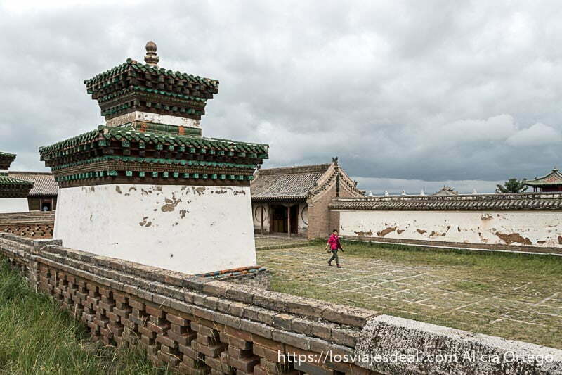 tumba antigua con dos tejados y una mujer vestida de rojo andando al lado y nubes de tormenta encima en karakorum