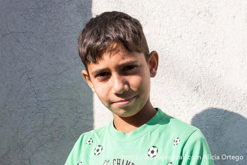 retrato de niño con sudadera verde con dibujos de balones de fútbol en la experiencia con los gitanos de bulgaria