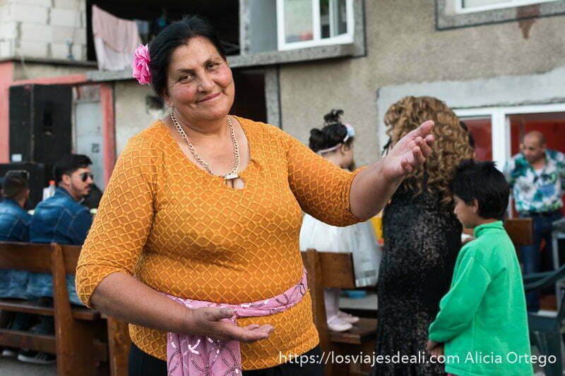 mujer gitana con gersey naranja y pañuelo rosa anudado a la cintura pelo negro y flor rosa en el pelo sonriente