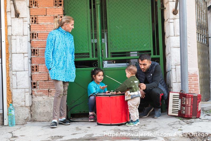 padres con el pequeño tosko tocando el tambor a la puerta de casa y la pequeña oli jugando con él. El acordeón está a un lado en el suelo