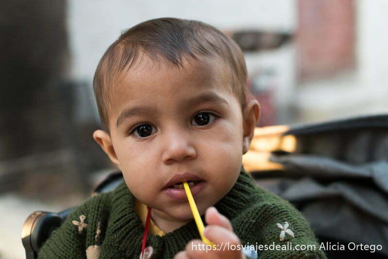 bebé tosko con un palito amarillo en la boca tiene los ojos almendrados y oscuros y los labios gruesos