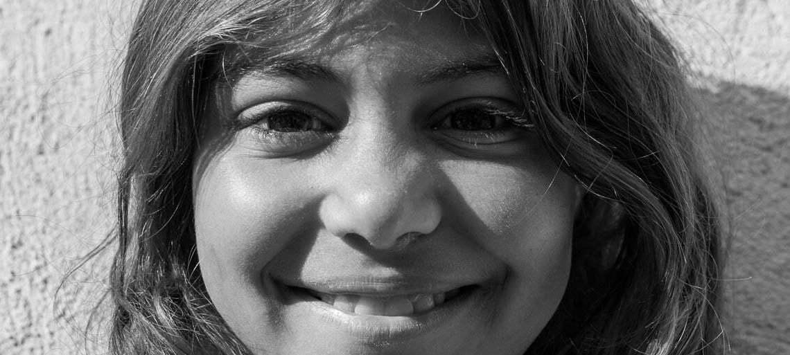 retrato de niña gitana sonriente mirando de frente a la cámara en blanco y negro