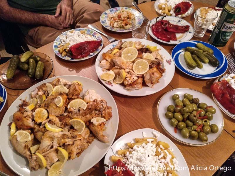 mesa llena de platos con pollo asado, pepinillos, aceitunas, patatas fritas y pimientos asados en mi experiencia con los gitanos de bulgaria