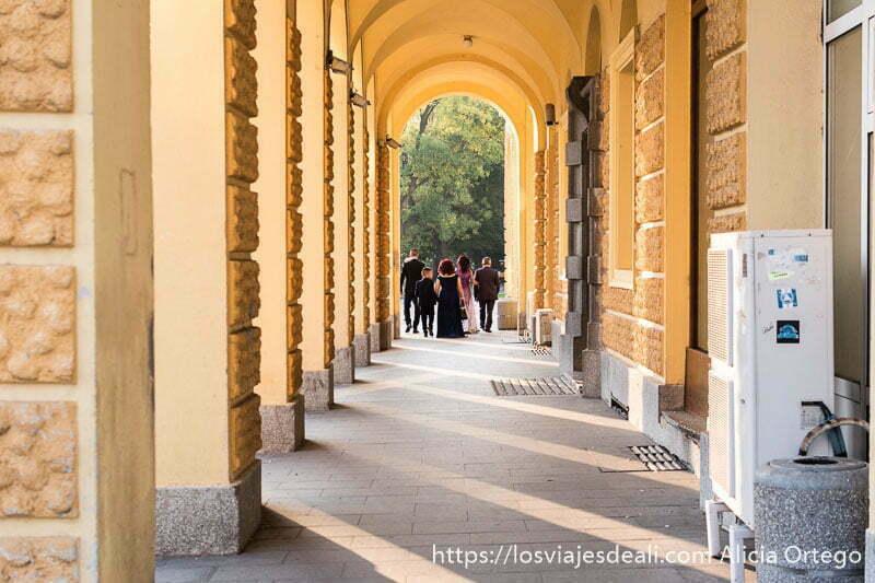 grupo de cinco personas vestidas de boda al fondo de un pasillo formado por arcos pintados de color naranja en sliven