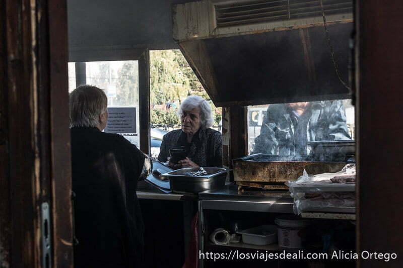 puesto de carne a la brasa visto desde atrás con una señora haciendo pedido en la ventanilla y la parrilla humeante a un lado
