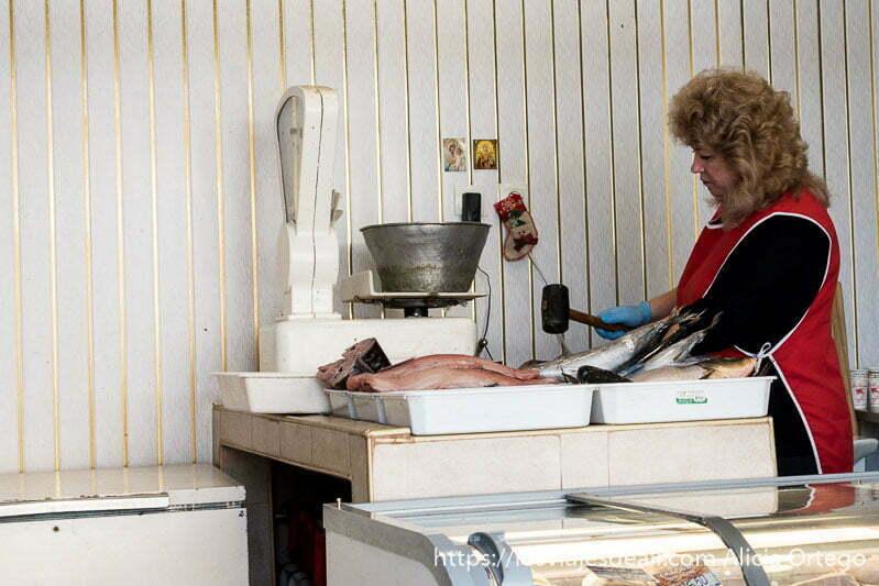 pescadera dando con un martillo a los peces en el mostrador y al lado una báscula antigua y dos estampitas de la virgen en sliven