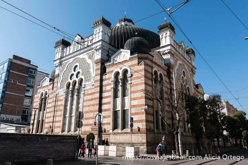 exterior de la sinagoga de sofía con cúpulas de color negro y fachada de mármoles a rayas horizontales