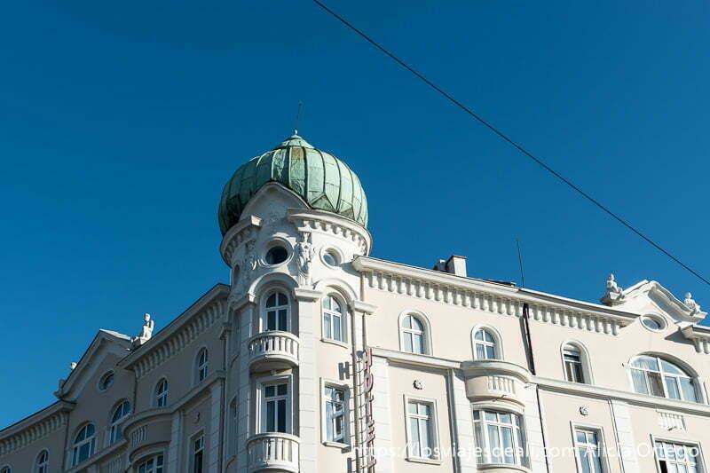 esquina de edificio con cúpula color verde sobre cielo azul