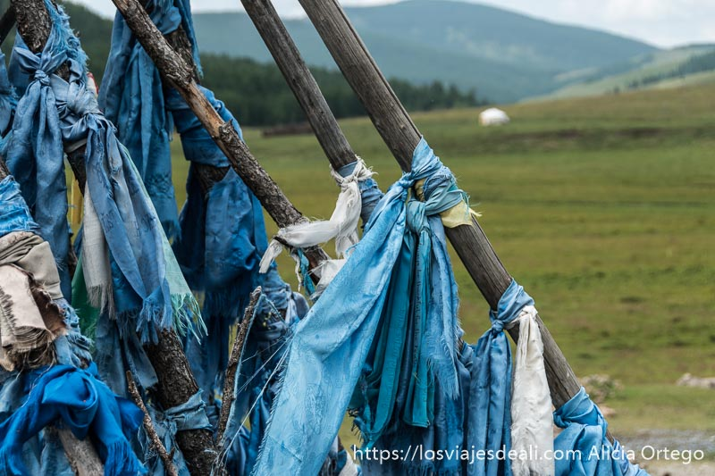 pañuelos de seda de color azul anudados en palos y detrás valle verde con montañas y bosque en mongolia central
