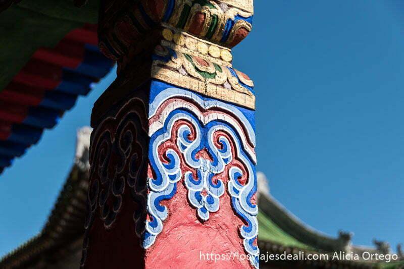 detalle de una columna del monasterio de tsenserleg con dibujos ondulados pintados de rojo y azules