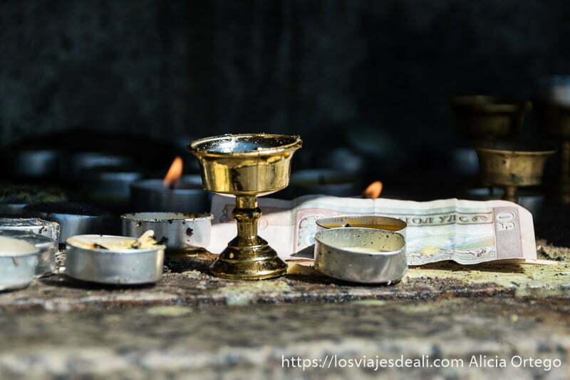 velas y dinero en billetes como ofrendas al pie del buda de tsenserleg en mongolia central