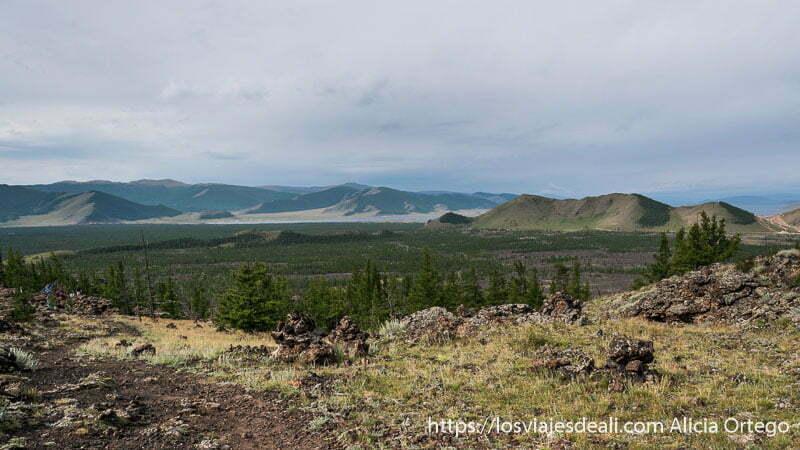 panorámica desde la cima del volcán con montañas volcánicas al fondo y un pedacito del lago blanco en el valle de khorgo en mongolia central