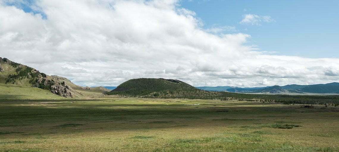 valle de khorgo con el volcán y delante un gran prado de hierba en mongolia central