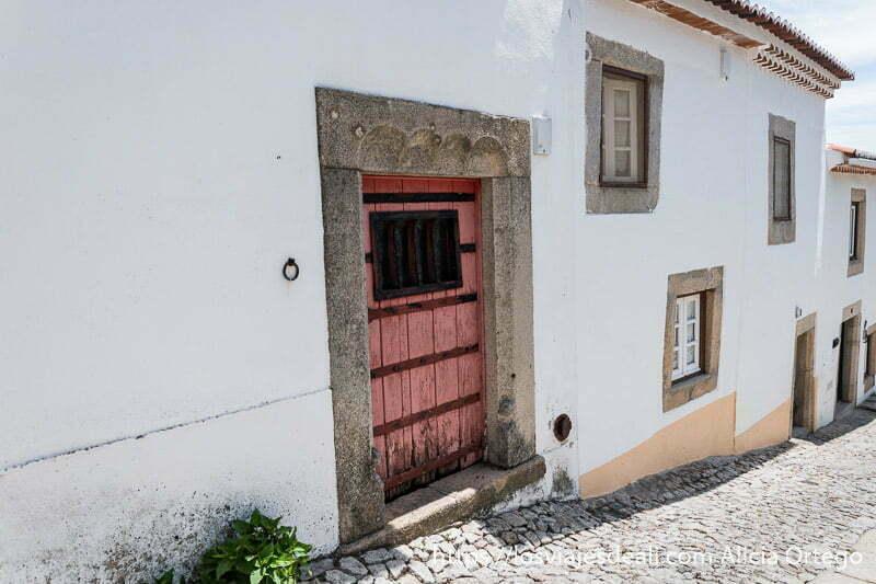 calle empedrada con puertas y ventanas enmarcadas en piedra y la puerta más próxima pintada de rojo