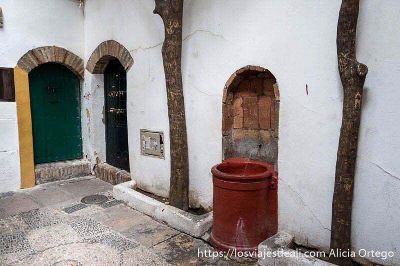 calleja del pañuelo con una fuente pintada de rojo y dos puertas de madera con arco de ladrillo visitar córdoba