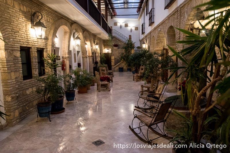 patio del hotel posada de vallina de córdoba con sillas de hierro y paredes de ladrillo y muchas plantas
