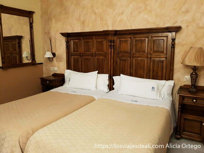 habitación doble del hotel posada de vallina con cabecero de madera oscura y espejo a juego en la pared