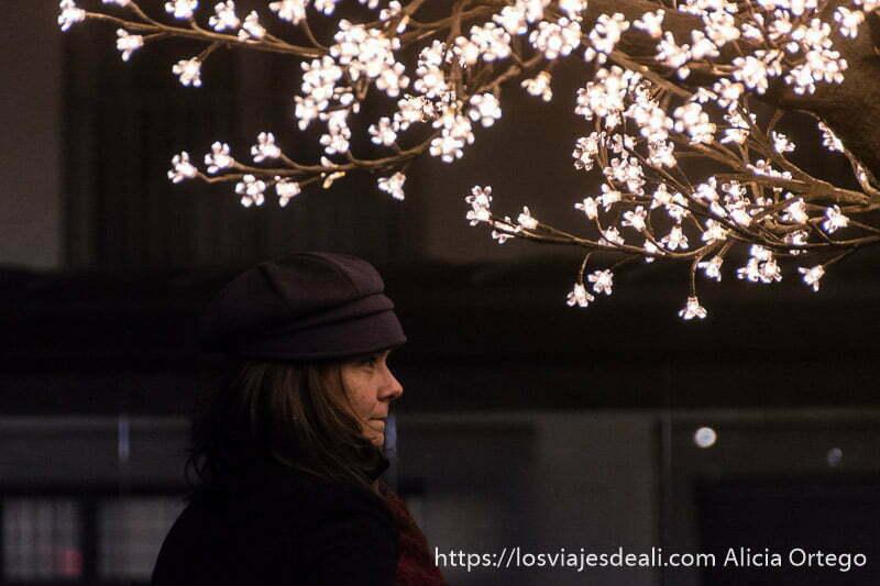 chica con gorra negra mirando el espectáculo de luces de biarritz bajo un árbol con flores de lucecitas