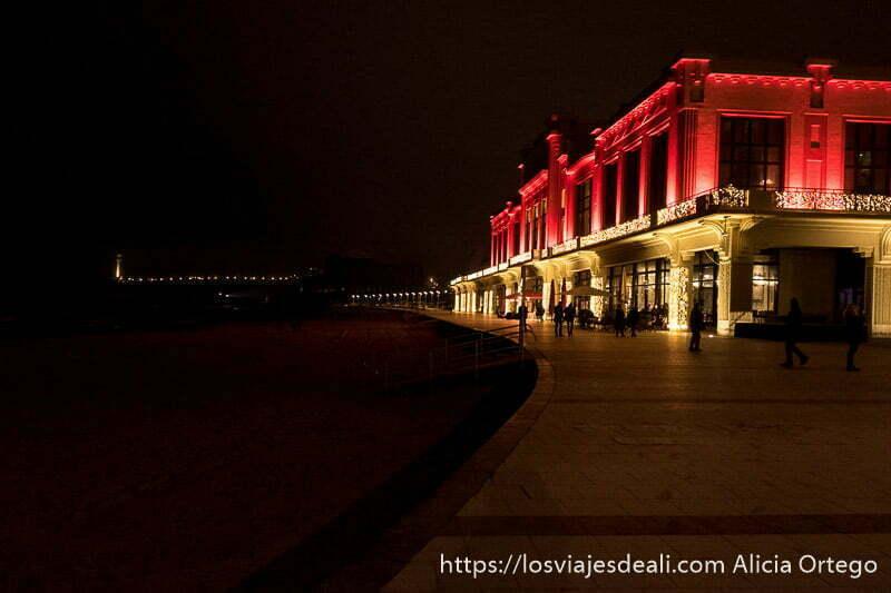 edificio del casino iluminado de amarillo y rojo y la izquierda el faro al fondo en la excursión a san juan de luz y biarritz