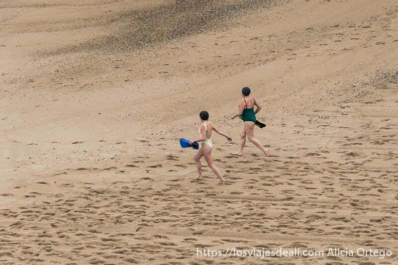 dos mujeres con bañador, gorro y aletas en la mano corren por la playa de camino al mar