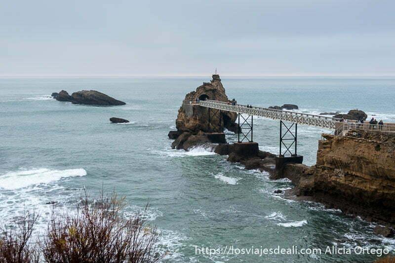 pasarela eiffel con roca de la virgen al fondo y mar medio en calma con cielo nublado en biarritz